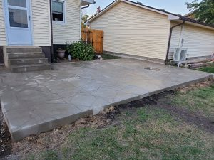 a concrete patio with a hole for firepit