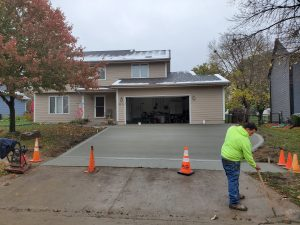man spreading the cement on driveway