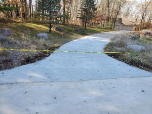 a concrete walkway with grass on the sides