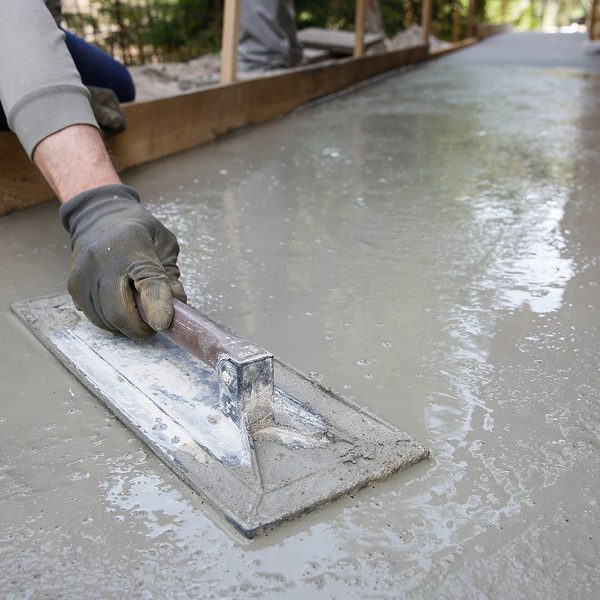 mason leveling and screeding concrete floor base with square trowel in front of the house