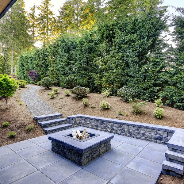 new modern home features a backyard with rectangular concrete fire pit framed by slate pavers and overlooking the lush garden.