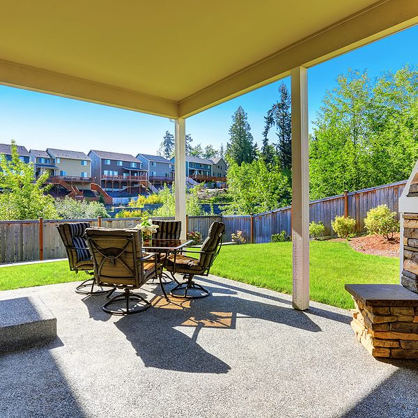 cozy covered patio with stone trim fireplace. glass top patio table and comfortable chairs with stripped covers.